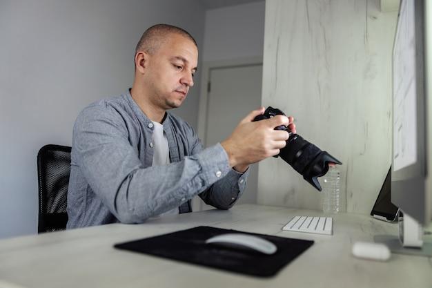 Un photographe expérimenté observe la matière première sur un appareil photo rouge avec un objectif qu'il a fait lors de la prise de vue photo