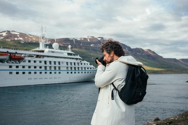 Un photographe fait des photos d'un bateau de croisière dans le fjord