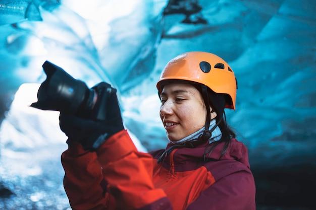 Photographe féminin dans la grotte de glace, islande