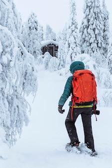 Photographe féminin marchant vers une cabane dans les bois enneigés
