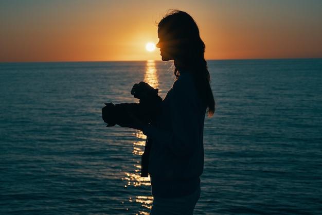Photographe femme avec appareil photo au coucher du soleil et mer en arrière-plan
