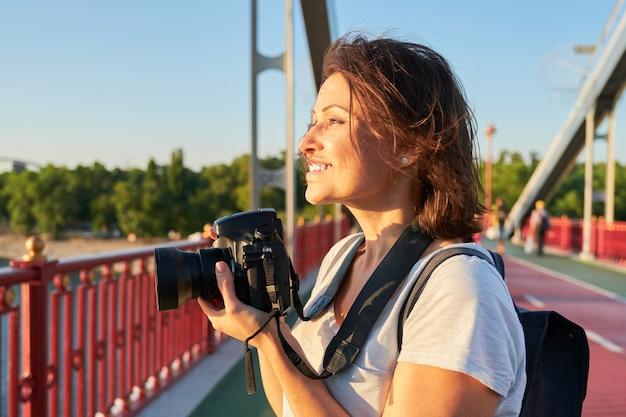 Photographe femme mûre avec appareil photo prenant photo