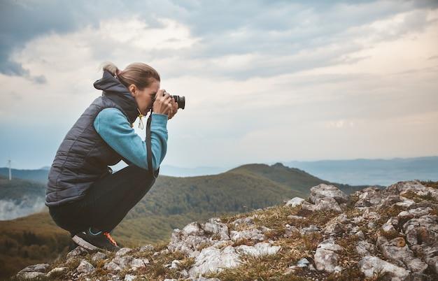 La photographe de femme prend une photo du paysage de montagne