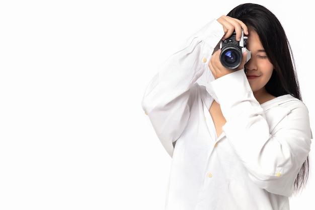 Photographe femme travaillant en studio. photographie de femme asiatique en action sur fond blanc. fille portant une chemise blanche tenant un appareil photo vintage à la main sans espace de copie.