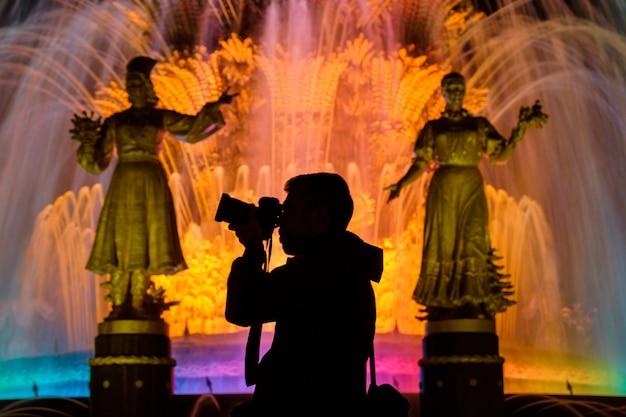 Photographe sur le fond des fontaines au vdnh la nuit
