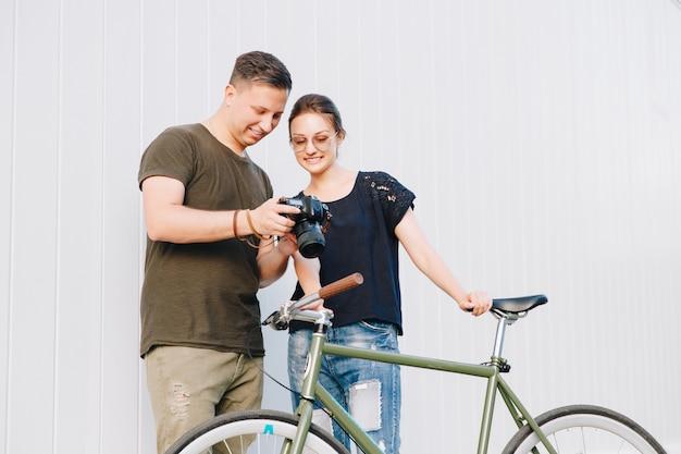 Photographe heureux et jolie femme vérifiant les photos après une séance photo avec vélo rétro, debout sur un mur blanc. en plein air.