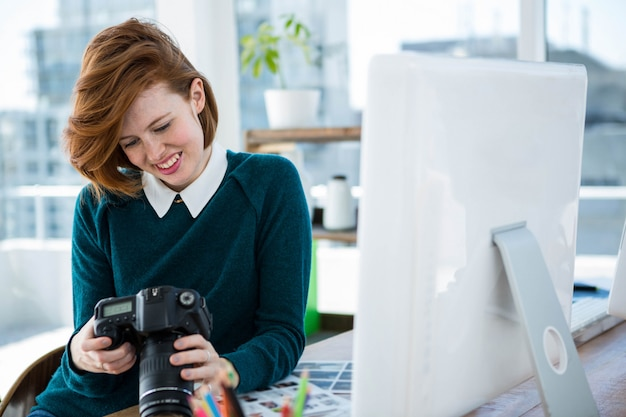 Photographe hipster souriant, assise à son bureau, regardant son appareil photo