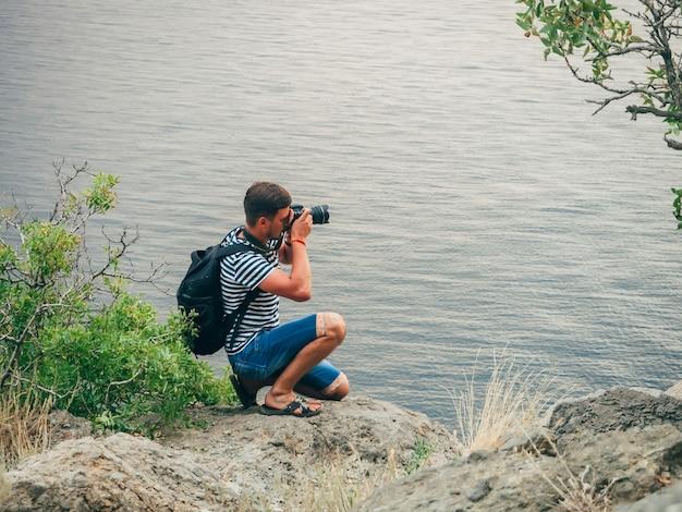 Photographe homme au bord de la rivière ou de la mer