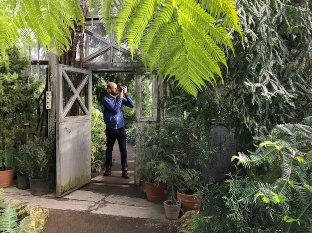Photographe homme barbu prenant une photo à la caméra dans une serre, debout avec une vieille porte en acier ouverte sur une journée ensoleillée.
