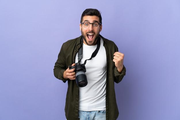 Photographe homme sur mur violet célébrant une victoire en position de vainqueur