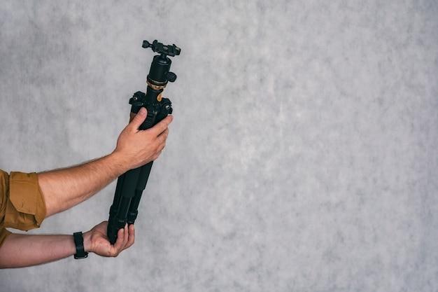 Un photographe homme tient un trépied professionnel dans ses mains pour prendre des photos et des vidéos.