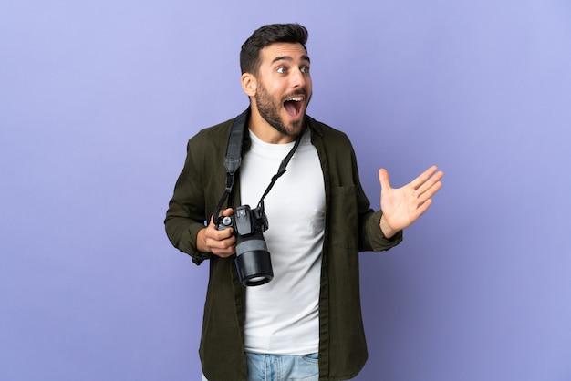 Photographe homme sur violet isolé avec une expression faciale surprise