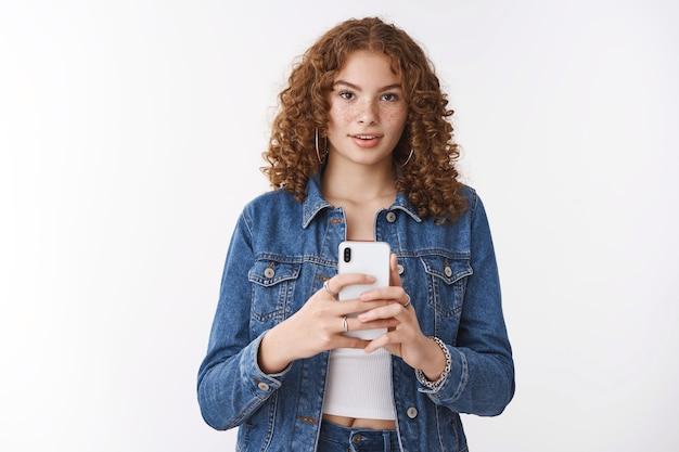Photographe indépendant attrayant créatif smm fille rousse tenant un smartphone regarde fasciné prendre une photo en vous photographiant à l'aide de l'appareil photo du téléphone, debout sur fond blanc concentré