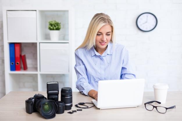 Photographe de jeune femme s'asseyant avec l'équipement informatique et de photographie dans le bureau moderne