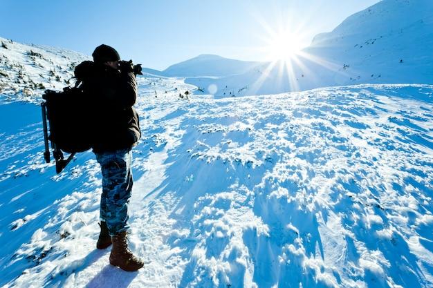Photographe jeune homme en vêtements d'hiver debout et faire photo au soleil