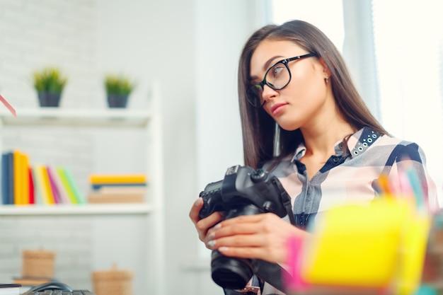Photographe jolie jeune femme avec caméra au bureau