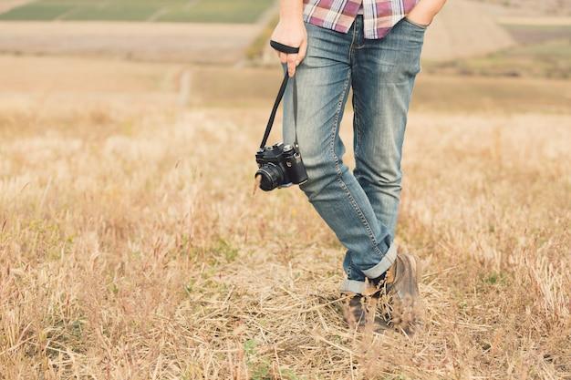 Photographe mâle attrayant à l'extérieur au coucher du soleil