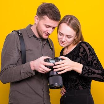 Photographe et mannequin vérifiant des photos sur l'appareil photo