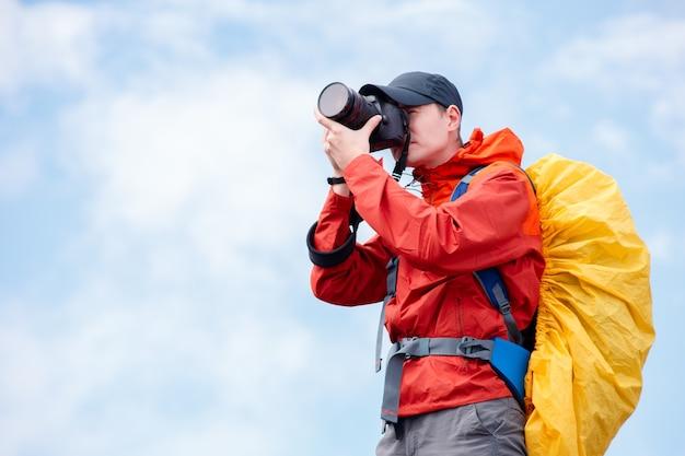Photographe masculin avec appareil photo et sac à dos sur ciel nuageux