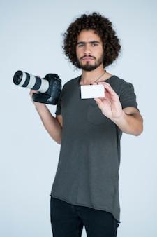 Photographe masculin montrant la carte de visite en studio