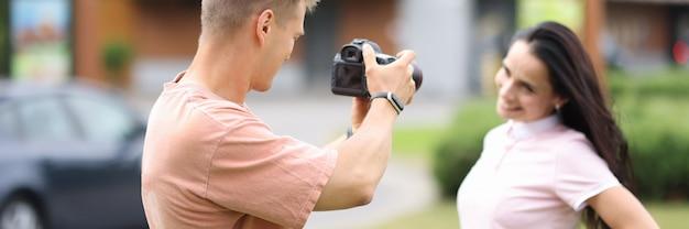 Le photographe masculin photographie le modèle féminin dans la rue.