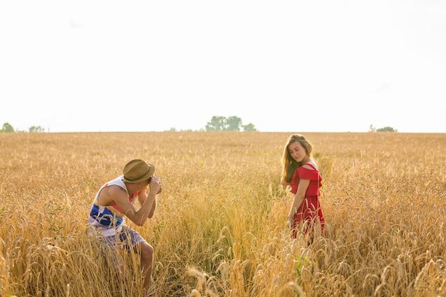 Photographe masculin prenant des photos d'une jeune femme debout dans le champ. couple, apprécier, jour, nature