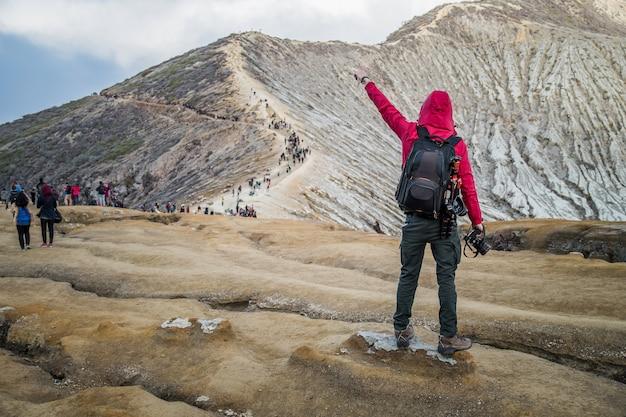 Photographe masculin avec sac à dos debout au sommet d'une montagne et profiter du lever du soleil, volcan coloré kawah ijen