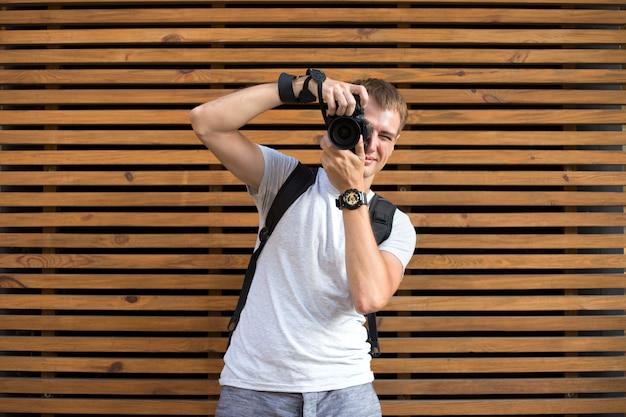 Photographe masculin sans visage avec appareil photo reflex numérique sur le fond en bois