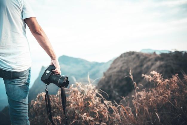 Photographe masculin tenant un appareil photo reflex numérique prêt à prendre des photos de paysages et de paysages de montagne
