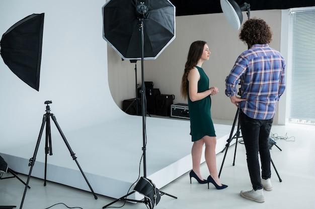 Photographe et modèle féminin examinant les photos capturées dans un appareil photo numérique