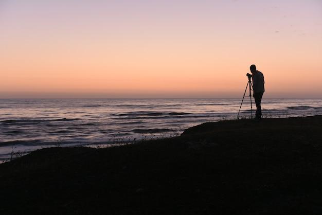 Photographe nature au bord de l'océan à l'aube