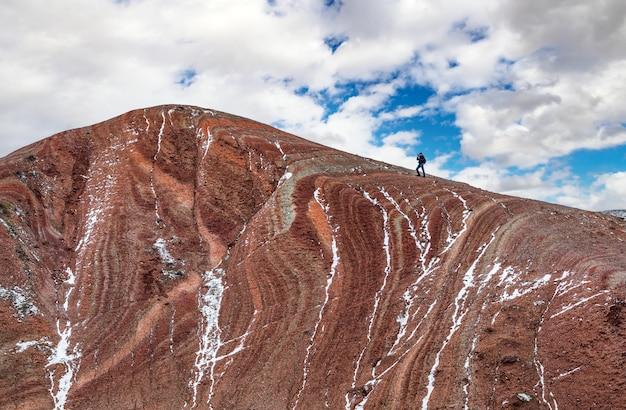 Un photographe de la nature au sommet de la montagne prend une photo du paysage