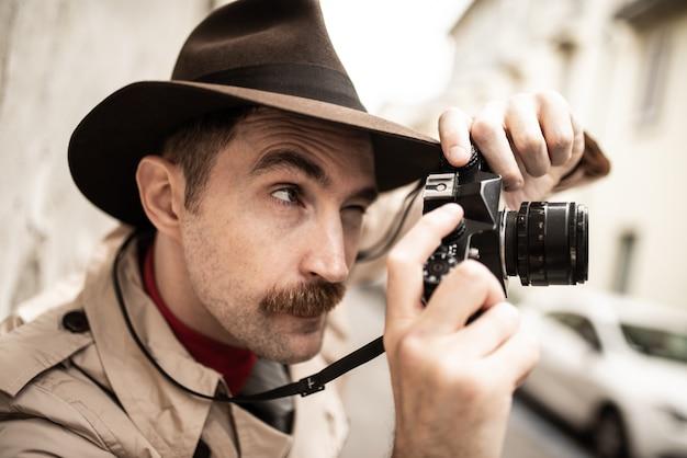 Photographe paparazzo à l'aide d'un appareil photo dans une rue de la ville