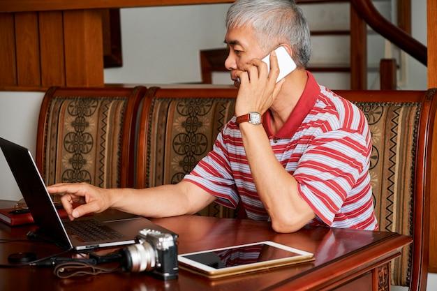 Photographe parlant au téléphone à la maison