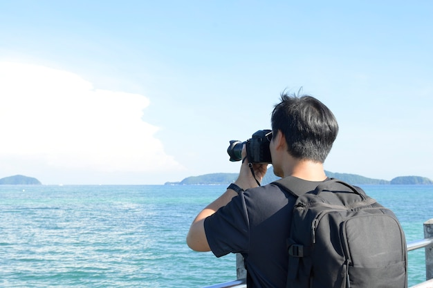 Photographe de paysage fait des photos de la mer sur la plage déserte