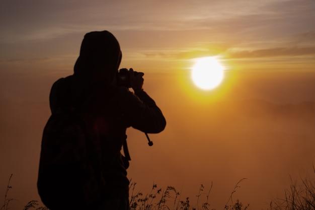 Un photographe photographie l'aube du soleil sur le volcan batur. bali, indonésie