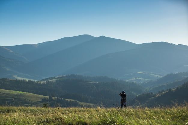 Un photographe photographie un paysage de montagne avec dans la soirée