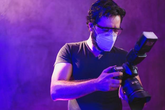 Photographe portant un masque kn95 avec une caméra professionnelle dans les coulisses de la production vidéo, concept de protection contre les coronavirus