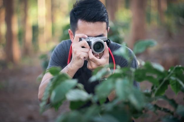 Photographe prenant une photo dans la forêt