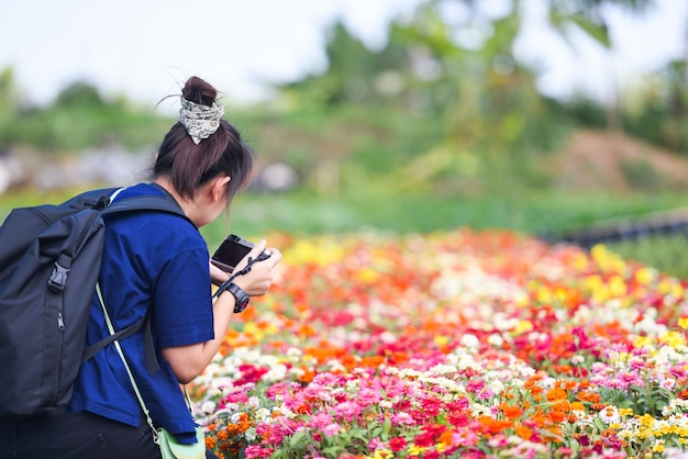 Photographe prenant une photo et tirant une fleur fleurie dans le jardin