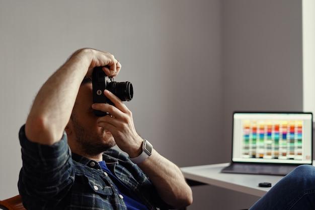 Photographe prenant une photo tout en regardant la caméra