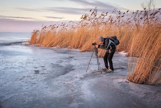 Le photographe prend une photo du coucher du soleil sur un lac gelé