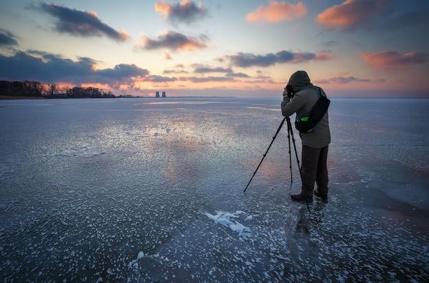 Le photographe prend une photo du coucher du soleil sur une rivière gelée en hiver