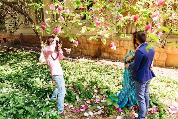 Un photographe prend des photos d'un couple amoureux près de magnolia et du bâtiment