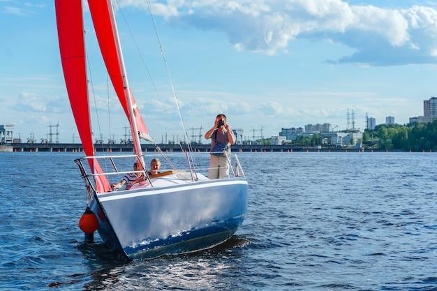 Le photographe prend des photos du bord du yacht avec des voiles écarlates sur le réservoir