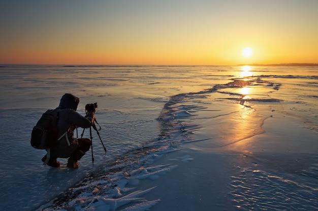 Le photographe prend des photos sur la glace pendant le coucher du soleil