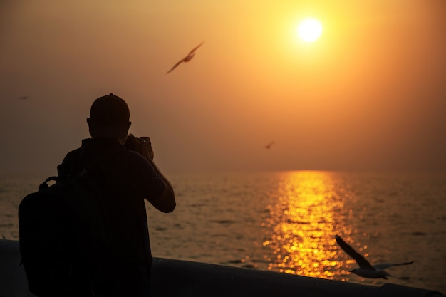 Photographe prendre une photo au coucher du soleil