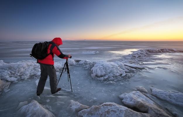Photographe prendre des photos sur la rive du fleuve en hiver