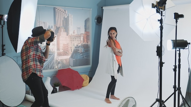 Photographe professionnel demandant au mannequin de changer de pose tout en faisant une séance photo en studio