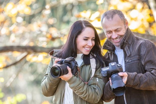 Photographe professionnel enseigne la photographie à son élève à l'extérieur, tous deux souriant à la photo dans son appareil photo.